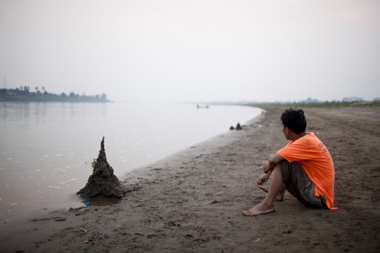 Young man watching dawn at the Mekong.