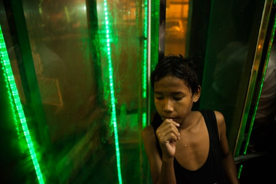 A young boy sucks his thumb in an elevator at the Shwedagon Pagoda.