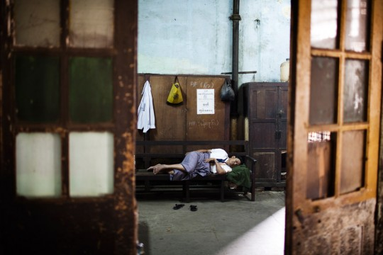 An employee of the Yangon railway station is taking a nap in his office.