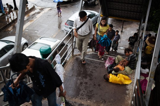 A woman is seen begging with her children on a stairway in downtown Yangon.